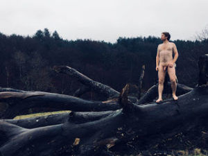 naked male on a fallen tree