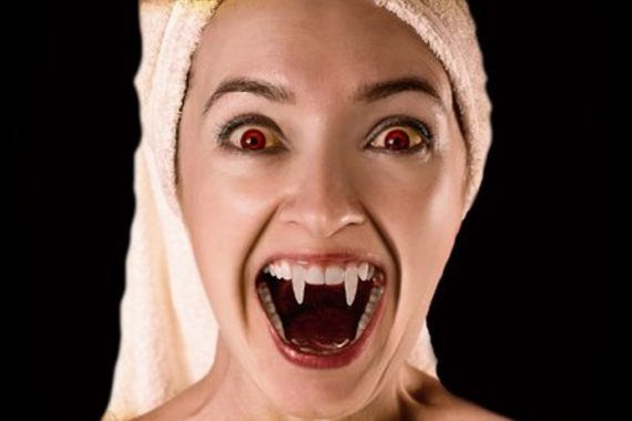 Head & shoulders of woman showing vampire fangs