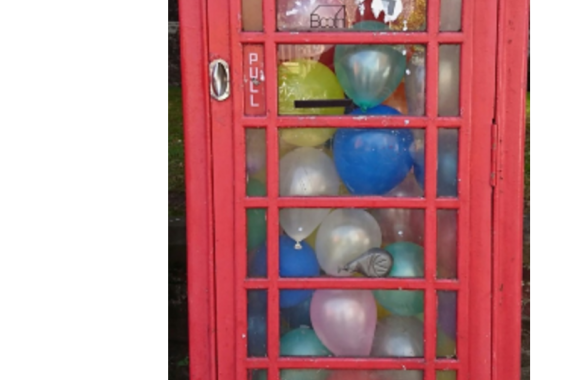 phone box filled with balloons