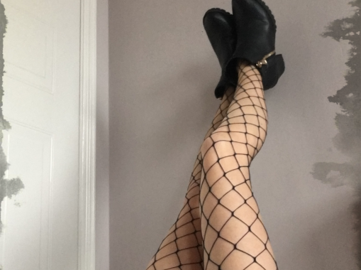 Legs in whalenet tights against wall